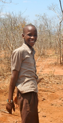 Emmanuel leading us to his village.  He's still wearing his school uniform.