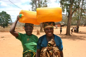 Miriam and Maria bringing more water to top off the school's daily supply.